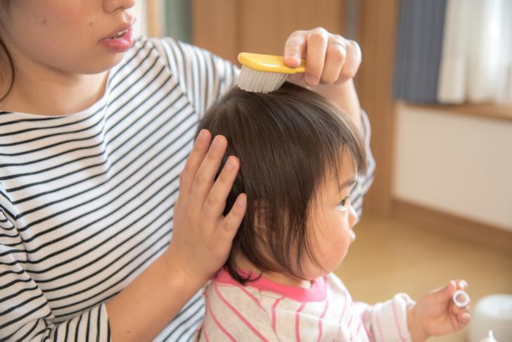 髪をとかしてもらう赤ちゃん