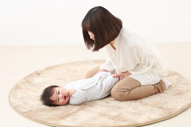 赤ちゃんに服を着せるママ
