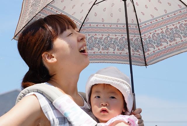 抱っこひもで赤ちゃんを抱っこしているママ