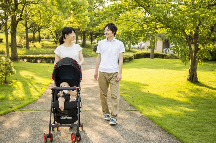 公園でベビーカーを押す若い夫婦