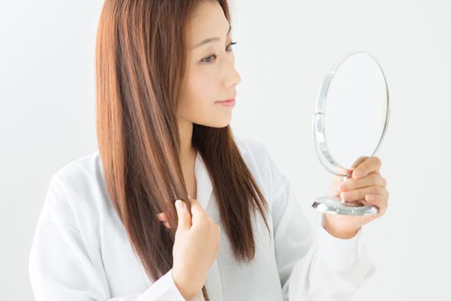 鏡で髪をチェックする女性